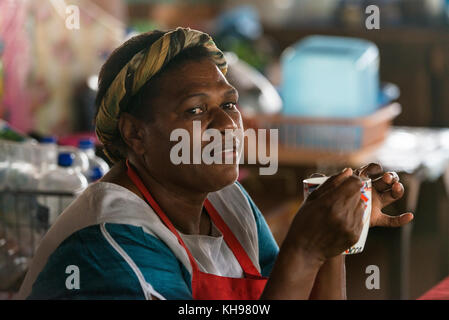 Joanna drinking a cup of hot water. Joanna works at Port Vila Fruit and Vegetable Market, Vanuatu. - Stock Photo