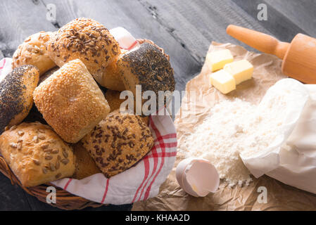 Baking theme image with a bunch of mixed buns, in a wicker basket, with flour, eggs, and butter near it, on a black - Stock Photo
