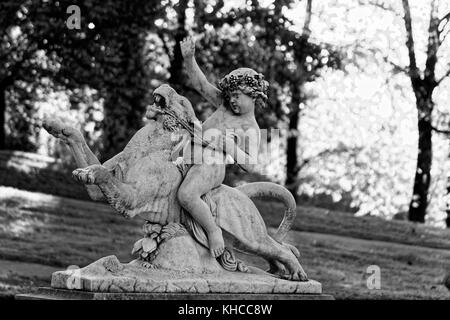 The  Statue of young boy riding a wild animal like lion in Lancut Castle park of Lubomirski family, Subcarpathian - Stock Photo