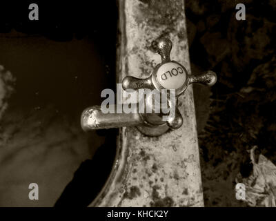 A chrome tap with a porcelain cold cap on a old cast iron bath with filthy water inside the bath. Left outside in - Stock Photo