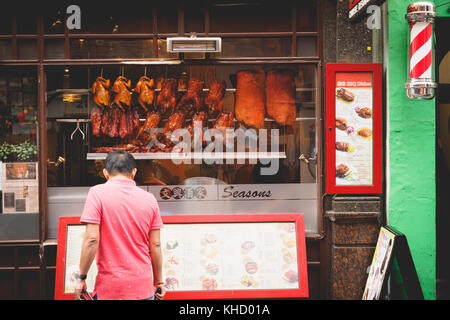 Crispy ducks hanging in a Chinese restaurant window in Chinatown. London, 2017. Landscape format. - Stock Photo