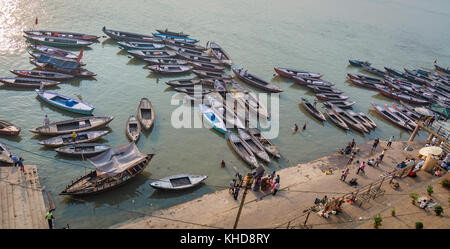 Varanasi ghat aerial view of multicolored wooden boats lined up at the Ganges river ghat with tourists and vendors. - Stock Photo