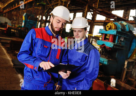Two workers discuss a construction project - Stock Photo
