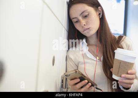 Young woman having a conversation on her smart phone holding a coffee cup in an office. - Stock Photo