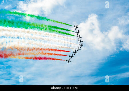 'freccie tricolori' acrobatic planes flight over sunny blue sky in summer dau making the italian flag in the sky - Stock Photo