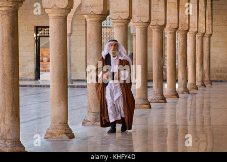 Man in ethnic clothes walking through the pillars in the courtyard of the Mevlidi Halil Mosque in Sanliurfa, Turkey. - Stock Photo