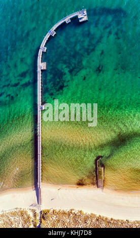 TOp down aerial view of historic fishing timber jetty in Port Philip bay off Port Melbourne beach on a sunny day. - Stock Photo