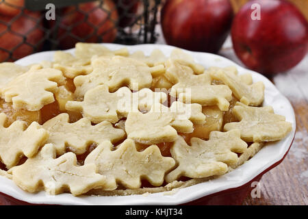 Raw, unbaked apple pie with top crust cut out in the shape of autumn leaves. Shallow death of field with selective - Stock Photo
