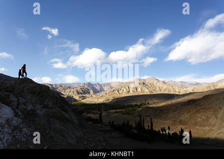 Woman and young boy silhouette standing on a hill above valley in Alchi, Ladakh, Jammu and Kashmir, India. - Stock Photo