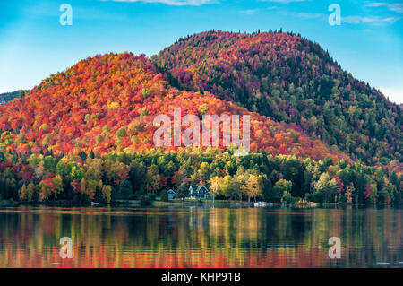 The hills covered with red maple forests behind a wooden house on the shore of a lake in Quebec, on a beautiful - Stock Photo