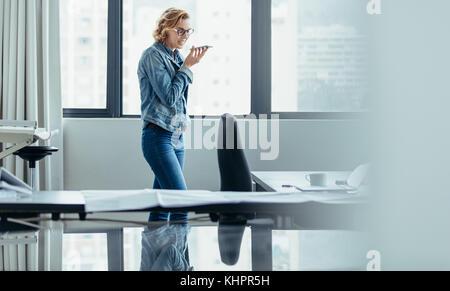Horizontal shot of businesswoman using mobile phone in office. Female architect talking on speaker phone. - Stock Photo