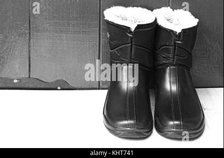 On the table near the wooden wall are warm waterproof men's boots for work or fishing. - Stock Photo