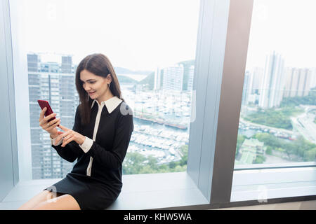 Woman sitting on windowsill using smartphone - Stock Photo