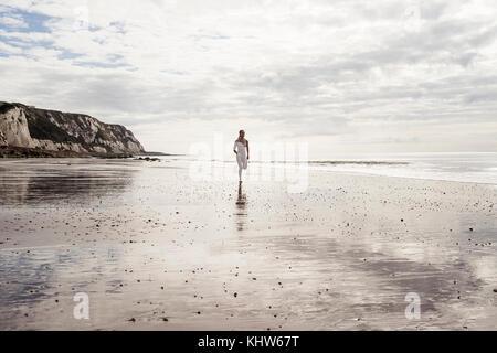 Young woman running along beach - Stock Photo
