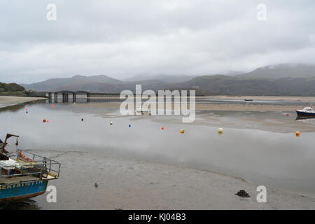 Tide out on the Afon Mawddach estuary on an overcast cloudy day looking from the harbour towards Barmouth railway - Stock Photo