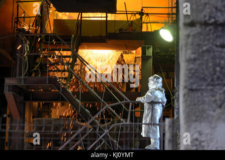 Molten Metal Pouring Out Of Furnace and Workers - Stock Photo