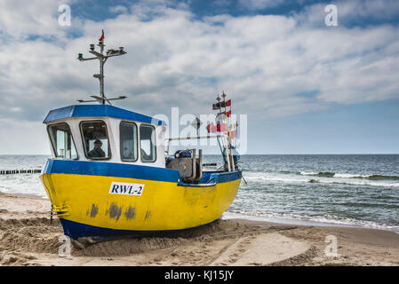 Fishing boat on a Baltic Sea beach in Rewal village, West Pomeranian Voivodeship of Poland - Stock Photo