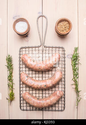 raw sausage for frying Grilled lie on the grid for cooking with rosemary and spices on a white wooden rustic background, - Stock Photo