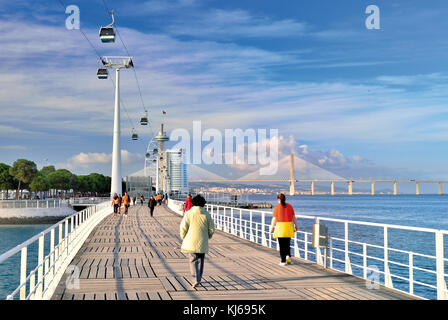 People passing pedestrian bridge surrounded by modern architecture, cable car lift and Vasco da Gama bridge - Stock Photo