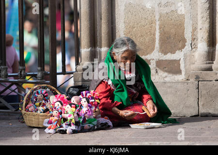 January 24, 2016 San Miguel de Allende, Mexico: an elderly street vendor eating while sitting on the ground - Stock Photo