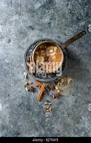 Vintage pot of traditional indian masala chai tea with ingredients above. Cinnamon, cardamom, anise, sugar over - Stock Photo