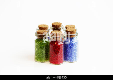 Six tiny glass bottles with a cork stopper, filled with a rainbow colours of beads, on a white background. - Stock Photo