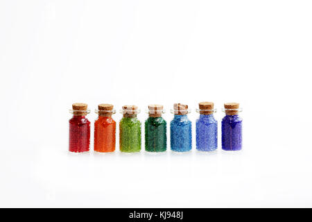 Seven tiny glass bottles with a cork stopper, filled with a rainbow colours of beads, on a white background - Stock Photo
