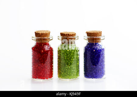 Three tiny glass bottles with a cork stopper, filled with a rainbow colours of beads, on a white background. Red, - Stock Photo