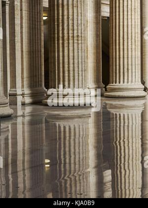 Partial interior view of architectural columns in greek revival style with reflections in highly polished floor. - Stock Photo