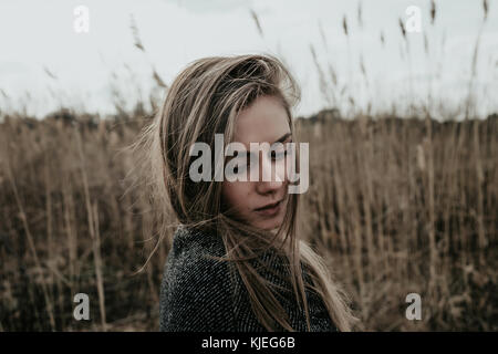 Young and beautiful woman with long blonde hair dressed in wool coat looking down over her shoulder. Girl standing - Stock Photo