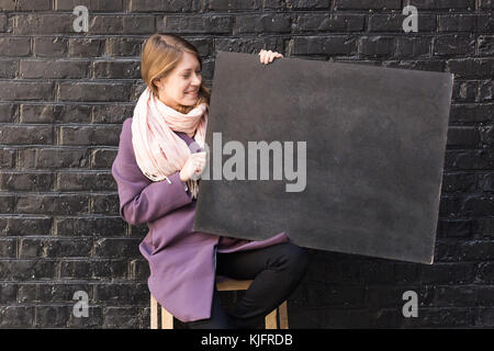 clothing, art, advertising concept. on the backgroun of brick wall there is lovely smiling woman dressed highly - Stock Photo