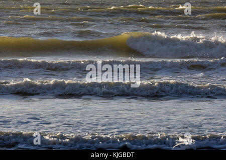 Waves crashing onto the shore on a rough weather day at sea and on the coast. Rollers and breaker hitting the beaches - Stock Photo