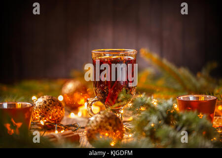 Warm red mulled wine in glass on Christmas background - Stock Photo