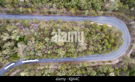 Aerial view of trucks as they approach a turn-back, or hairpin turn, among forest. - Stock Photo
