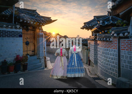 Back of two women wearing hanbok walking through the traditional style houses of Bukchon Hanok Village in Seoul, - Stock Photo