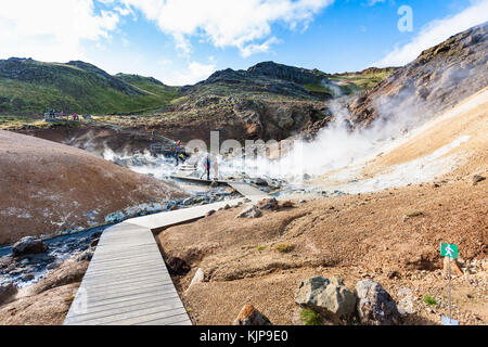 KRYSUVIK, ICELAND - SEPTEMBER 10, 2017: tourists at wooden pathway in geothermal Krysuvik area on Southern Peninsula - Stock Photo