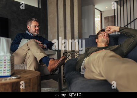 Stressed man listening psychologist's analysis. Male patient lying on sofa during psychotherapy session. - Stock Photo