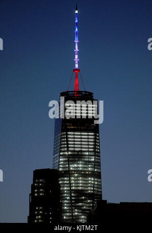 NEW YORK, NY - NOVEMBER 14: Empire State Building dark, World Trade Center lit in French flag colors. The 408-foot - Stock Photo