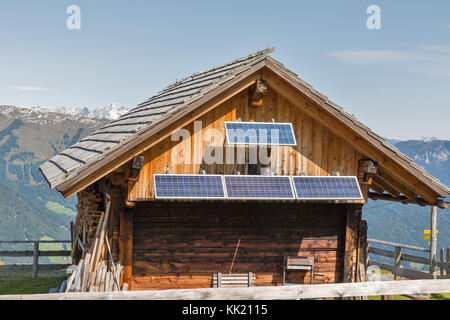 Wooden shepherd lodge with solar panels and Alpine mountain landscape in Western Carinthia, Austria. - Stock Photo