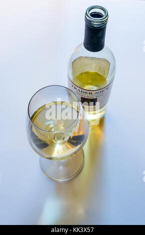 An open bottle and glass of Trader Joe's Charles Shaw Blend of Pinot Grigio -- three-buck chuck - Stock Photo