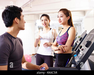 young asian man and women chatting in gym while taking a break. - Stock Photo