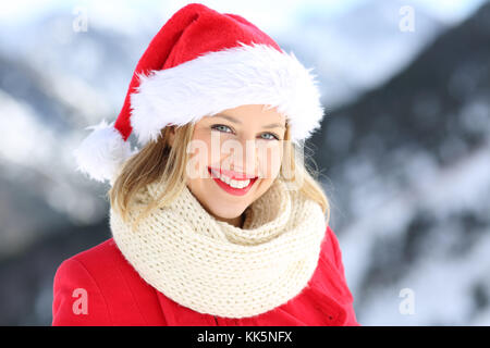 Portrait of a happy woman posing with santa claus hat in christmas holidays with a snowy mountain in the background - Stock Photo