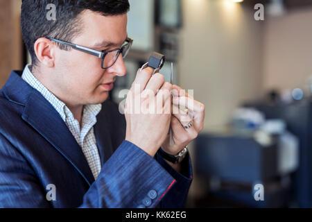 Jeweler examining diamond through loupe - Stock Photo