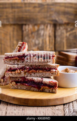 Peanut butter and jelly sandwich with whole wheat bread on rustic wooden table - Stock Photo