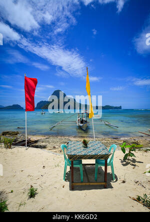 A table of outdoor restaurant on beach in Coron Island, Philippines. - Stock Photo