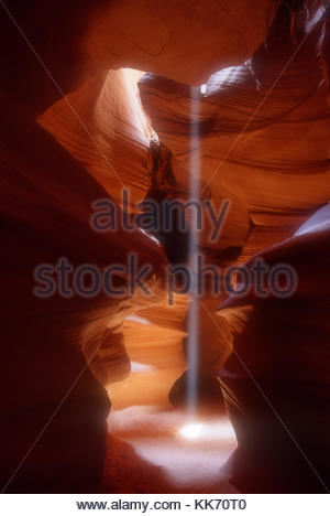 A vibrant shaft of light shines like a spotlight on the floor of Antelope Canyon in Page, Arizona. Antelope Canyon - Stock Photo
