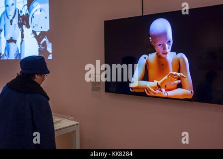 Elderly woman looking at television screen showing female android / humanoid robot at exposition about robotics - Stock Photo