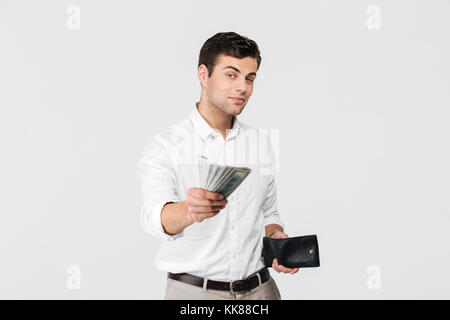 Portrait of a successful smiling man holding wallet and giving money banknotes isolated over white background - Stock Photo