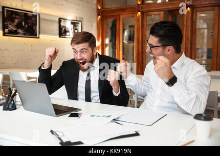 Two successful employees looking at a computer monitor on the table while expressing their achievement in the office - Stock Photo