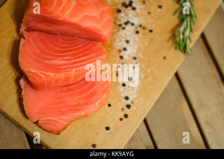 Sliced salmon fillet and pepper on cutting board - Stock Photo